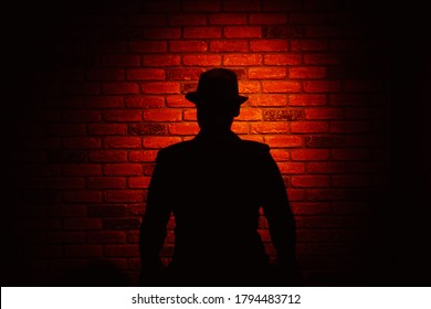 Silhouette of a man in a hat on a brick background. Noir, crime, detective.