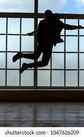 Silhouette of a man. He makes a jump in the dance