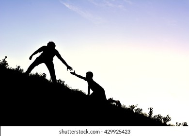 Silhouette of man helps a boy on mountain at the sky sunset
