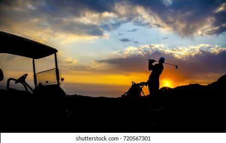 Silhouette of a man with his golf cart playing golf at sunset