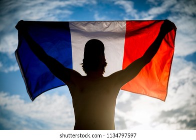 Silhouette of man holding backlit french tricolor in happy celebration