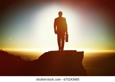 Silhouette man holding briefcase while walking against scenic view of mountain by sea against sky