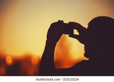 silhouette of a man holding a cellphone taking pictures outside during sunrise or sunset with a retro toned instagram filter
