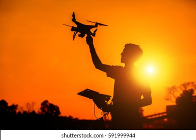 silhouette of the man holding Drone in sunset