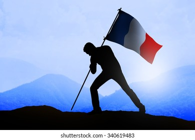 Silhouette of man holding france flag standing on the mountain