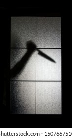silhouette of a man holding a knife behind the window