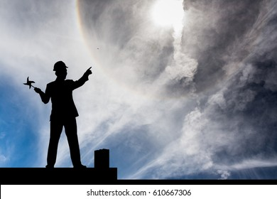 Silhouette of man holding wind turbine and point to the sun halo.