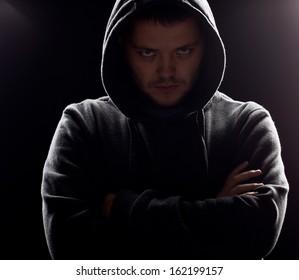 Silhouette of man in the hood or hooligan over dark