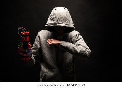 The silhouette of a man in the hood on a black background, his face is not visible, shows hands gesture and a time bomb. The concept of criminal terrorism