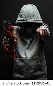 The silhouette of a man in the hood on a black background, his face is not visible, shows hands gesture and a time bomb. The concept of criminal