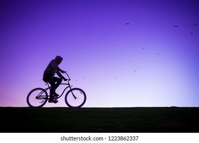 Silhouette of man in hoodie riding a beach cruiser bicycle against a glowing purple sky