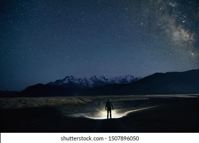 Silhouette of man is illuminating road with headlamp in the mountains under night sky with stars.