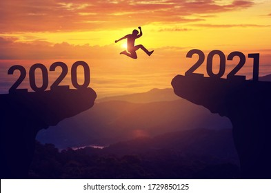 Silhouette man jump between 2020 and 2021 years with sunset background, Success new year concept.