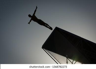 Silhouette man jump high diving