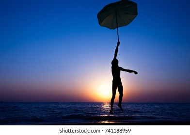 Silhouette of a man jumping against the setting sun on the beach with an umbrella in his hand
