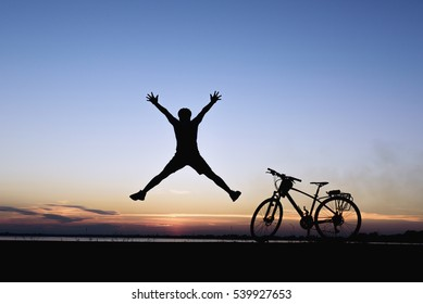 Silhouette of man jumping  with bicycle and sunset background.