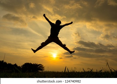 Silhouette of man jumping during sunset