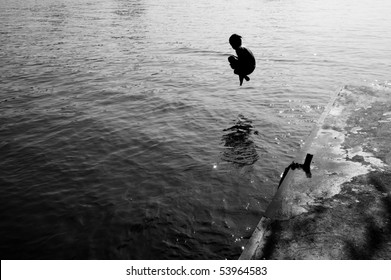 Silhouette of a man jumping into the sea