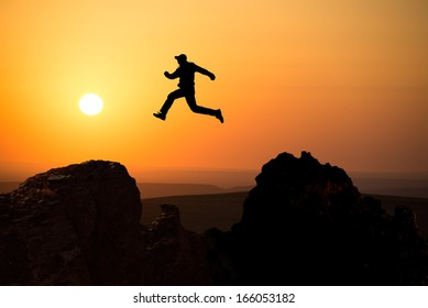 silhouette of a man jumping off a cliff in the direction of the bright sun