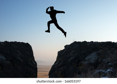 silhouette of a man jumping off a cliff in the direction of the morning