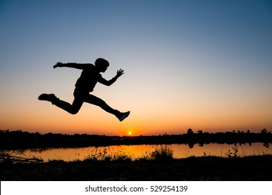 silhouette man jumping on sunset background