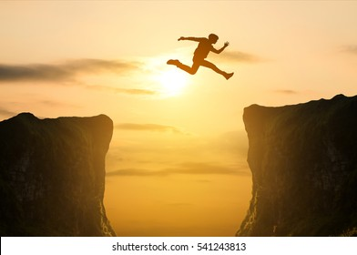 silhouette of man jumping over the cliff on sunset background, business concept idea