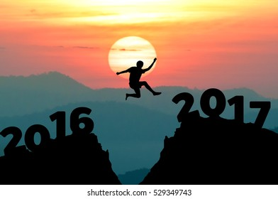 silhouette man jumps to make the word Happy New Year 2017 with sunrise.