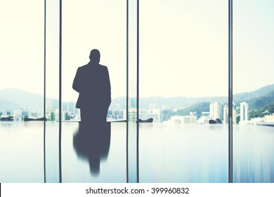 Silhouette of a man jurist is resting after hard work day, while is standing in private office near window with view of business center in New York.Copy space background  for your advertising content