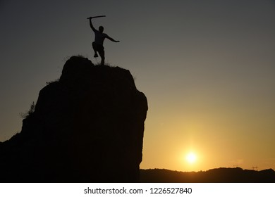 Silhouette of a man with katana exercising on edge of the cliff
