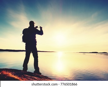 Silhouette of man keep memories with camera phone in his hand. Marvelous sunset at sea, smooth water level