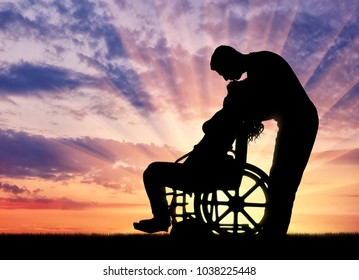 Silhouette of a man kissing a disabled woman in a wheelchair at sunset