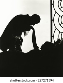 Silhouette of man kissing reclining woman's hand