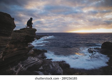 The silhouette of a man kneeling on a ledge looking out to sea as the sun peaks up over the horizon.