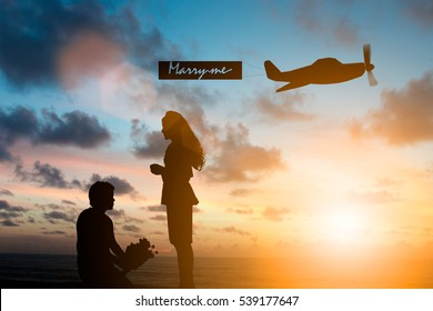 Silhouette man kneeling say Will you marry me in front of the woman he loves over plane bound with cloth wrote marry me over blurred nature.