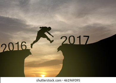 Silhouette of a man leaping across a crevasse from 2016 to 2017 for the concept of New Year 2017.