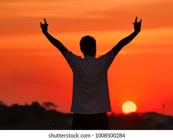 Silhouette man lifted their hands symbolising love over the head on background at sunset time.