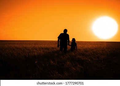 The silhouette of a man and a little girl in a field during sunset. Toned