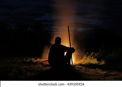 Silhouette of a man with a long stick sitting by the fire at night. Ancient priest sitting by the fire leaning on his staff and looked at the symbolic star in the sky.
