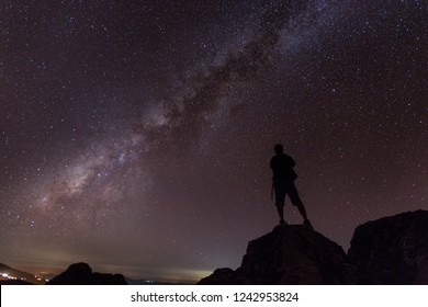 Silhouette man look at the milky way on the mountain.