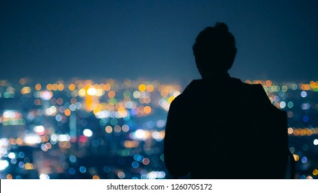 Silhouette Man looking to beautiful color of city night light from top of building at bangkok Thailand. Back view of young man.