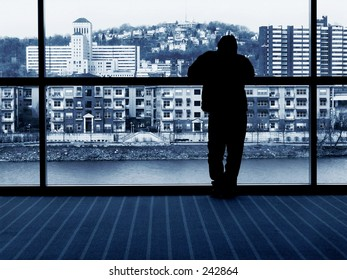 silhouette of man looking out window, city
