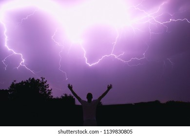 silhouette of the man of the magician summoning the lightning illuminating the night sky with bright flashes, the riot of the natural elements