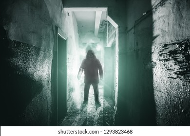 Silhouette of man maniac or killer or horror murderer with knife in hand in dark creepy and spooky corridor. Thriller atmosphere, toned