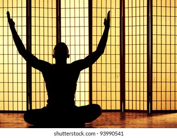 Silhouette of a man meditating and finding a zen moment
