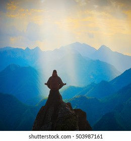 Silhouette of man meditating in sitting yoga position on the top of mountain above the misty valley. Zen, meditation, peace