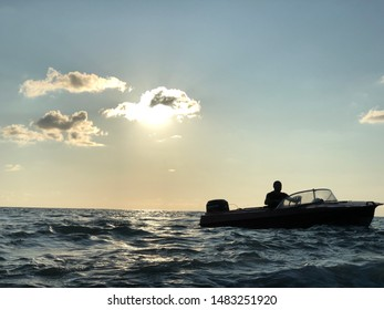 Silhouette of a man in a motor boat on a sunset background. A man on a boat floats in the sea off the coast. A view from afar, small people, blue sky, bright sun. Kobuleti, Georgia, August 3, 2019