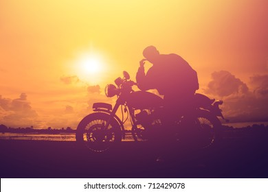 Silhouette of man and a motorcycle with sunset background.