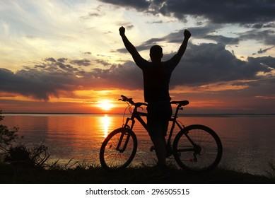 silhouette of a man with a mountain bike on the river bank at sunset