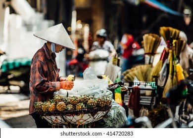 Silhouette of a man in the national Asian hat. Street vendor with a cart on the street. with pineapple tray