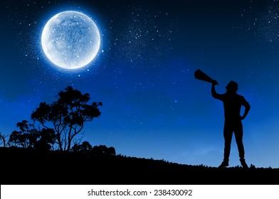Silhouette of man at night screaming in megaphone